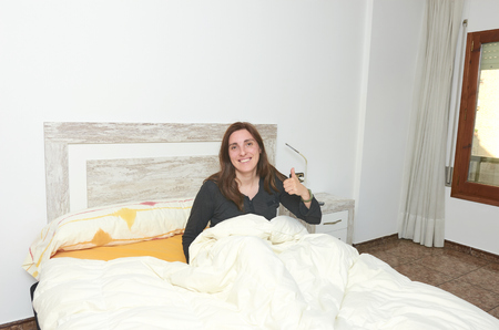 Happy woman smiling on bed with thumb up