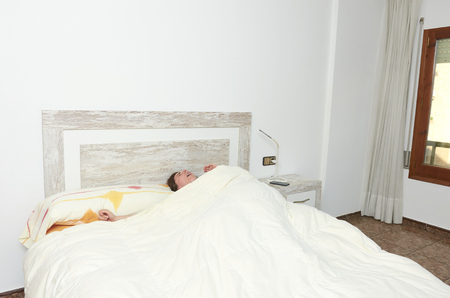 Woman stretching in bed after waking up Imagens