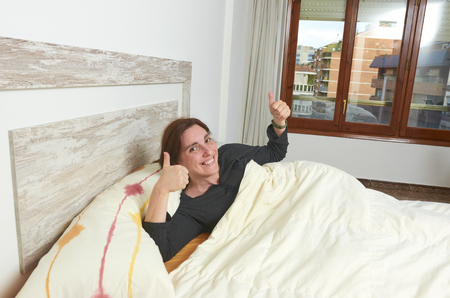 Happy woman smiling on bed with thumbs up