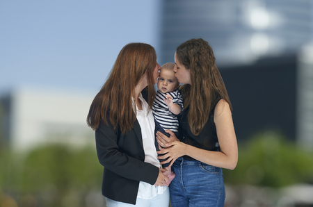 Lesbian mothers with their baby. Homosexual family, lesbian love Imagens
