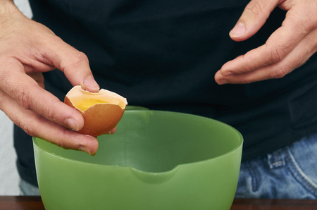 the cook separates the yolk in the egg Imagens