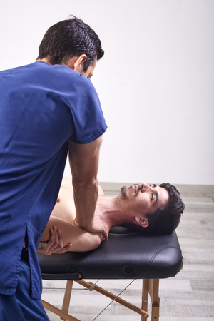 Young man having chiropractic shoulder adjustment. Physiotherapy, sports injury rehabilitation. Osteopathy, Alternative medicine, pain relief concept Imagens