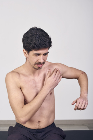 Young man with pain in the shoulder in a clinic Stock fotó