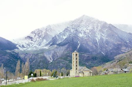 Pintoresco pueblo de la Vall de BoÃ, Pirineo catalán, España. Iglesia románica y montañas nevadas al fondo. Foto de archivo