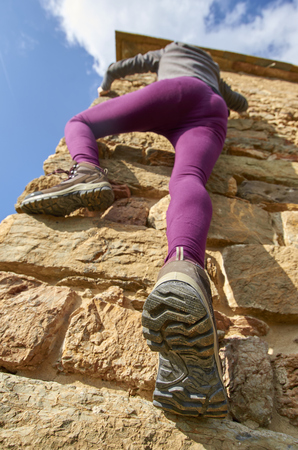 Young woman climbing on a stone wall