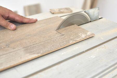 Skilled carpenter cutting a laminate wood, using a circular saw.
