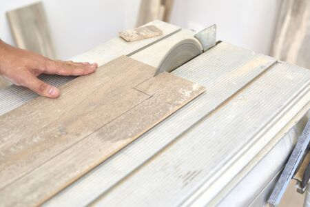 Carpenter cutting a laminate wood before to installing on the floor