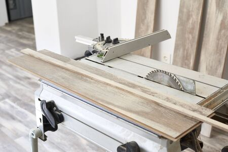 Machine of circular saw to cut wood. The process of installing laminate wooden on the floor. Home construction. Stock Photo