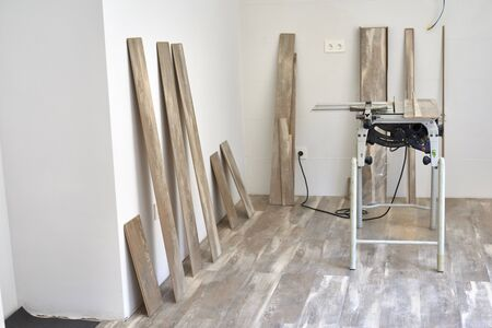 Machine of circular saw to cut wood. The process of installing laminate wooden on the floor. Home construction. Stockfoto