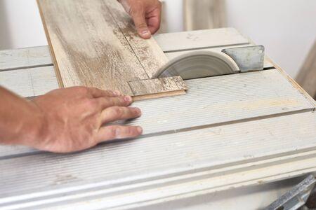 Carpenter on work putting laminate wood. Home construction. Stock Photo