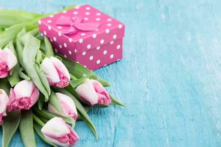 Bouquet of Tulips and gift box on turquoise rustic wooden background with copy space for message. Spring flowers. Greeting card for Valentines Day, Womans Day and Mothers Day holidays. Soft focus