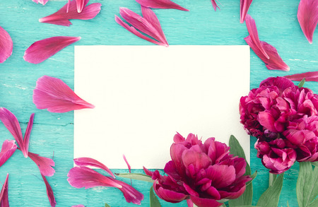 Red peony flowers on turquoise rustic wooden background with empty card for greeting message. Mothers Day and spring background concept. Holiday mock up. Top view.