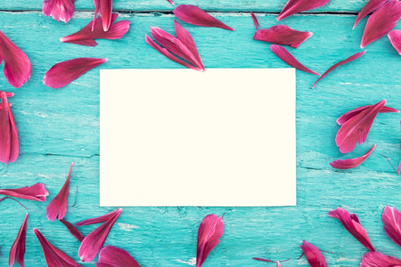 Empty card for greeting message on turquoise rustic wooden background with peony petals . Mother's Day and spring background concept. Holiday mock up. Top view.