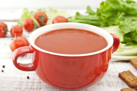 Tomato soup in red ceramic bowl on rustic wooden background. Healthy food concept. Soft view.