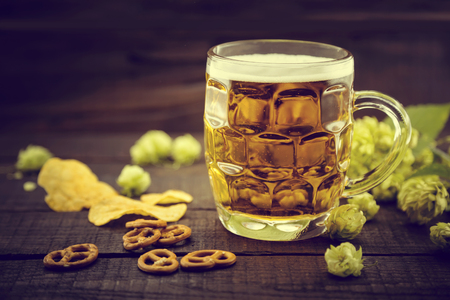 Beer and snacks on black wooden table. Draft cold beer in glass jar with green ripe hop cones. Still life. Friday concept. Oktoberfest background. Soft focus