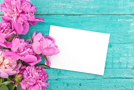 Bouquet of pink peony flowers on turquoise rustic wooden background with empty card for greeting message. Mothers Day and spring background concept. Holiday mock up. Top view.