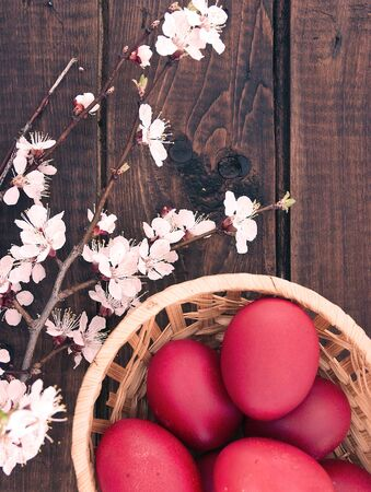 wooden basket: Basket with easter cake and red eggs on rustic wooden table. Top view. Stock Photo