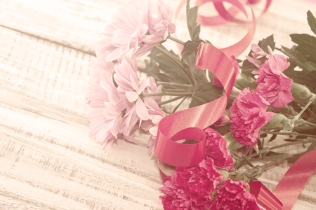 Bouquet of pink Chrysanthemum and Carnation flowers on rustic white wooden table. Vintage toned image. Soft focus.