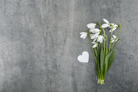 Bouquet von Schneeglöckchen auf grauem Stein Hintergrund mit Kopie Platz für Nachricht. Erste Frühlingsblumen Grußkarte für Valentinstag, Tag der Frau und Muttertagsfeiertage. Draufsicht Standard-Bild - 76230315