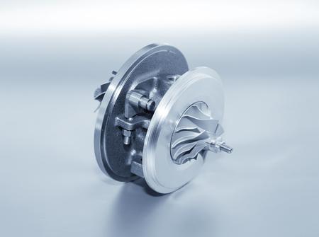 Turbocompressore su fondo metallico. Turbina per auto - parte del motore. Tonalità blu Archivio Fotografico