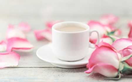 Cup of coffee on rustic wooden table in a frame of pink roses. Greeting card with flower. Soft focus. Stock Photo