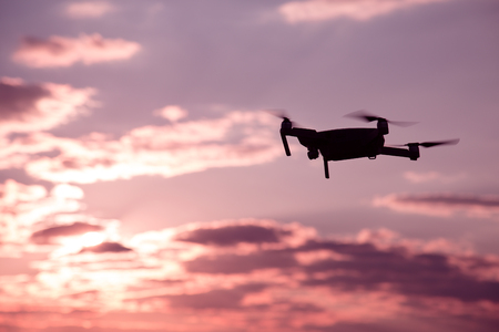 Silhouette of drone hovering in a colorful sunset. Toned image. Soft focus.