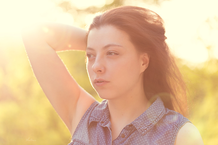 Attractive young woman with long brown hair enjoying hertime in the park with sunset in background Banque d'images