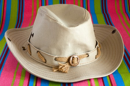 beach mat: Beige cowboy hat on striped beach mat