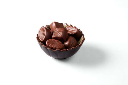 There are the chocolate candies in a nice bowl on a white background with shadow Stock Photo - 8801779