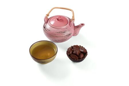 Composition with tea set that shows teakettle, tea in a cup and candies in a bowl on a white background with shadows.