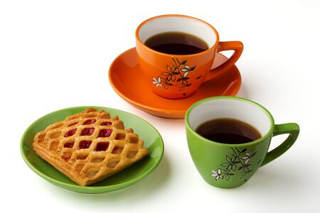 There are two cups with tea on the white background, orange and green. Also there are sweets on the saucer Stock Photo - 8801784