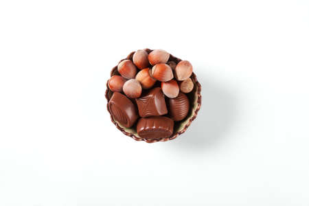 There are the chocolate sweets and nuts in a nice bowl on a white background.