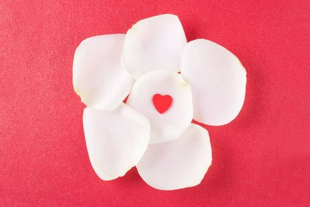 There are red heart on the centre of rose petals on the red background