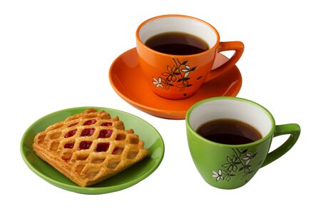 There are two cups with tea on the white background, orange and green. Also there are sweets on the saucer