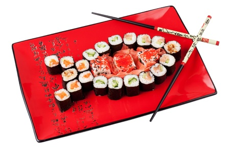 Sushi in the shape of the fish with chopsticks on the red plate. Stock Photo