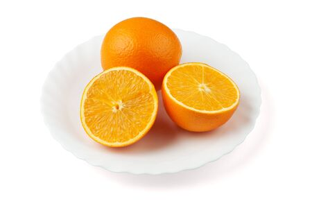 Two oranges on the white plate. One orange is sliced. Stock Photo