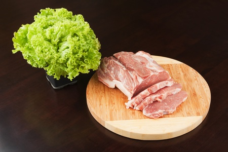 Meat on a cutting board and the bandle of the lettuce.