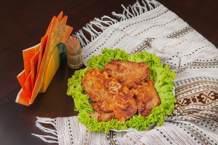 There are cutlets on the plate decorated with lettuce, napkins and wooden sticks on the dark brown table with cover. Stock Photo