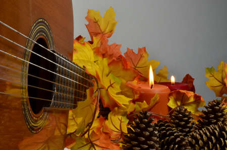 Guitar and Fall leaves with lit candles
