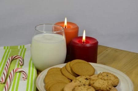 Cookies and milk with lighted candles photo