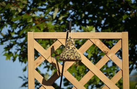 Birdfeeder on a backyard garden trellis Stock Photo