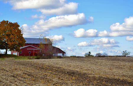 Home and barn near a plowed farmland