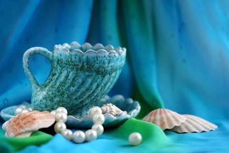Sea still-life with a cup, cockleshells and pearls
