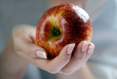 Apple in a female hand Stock Photo