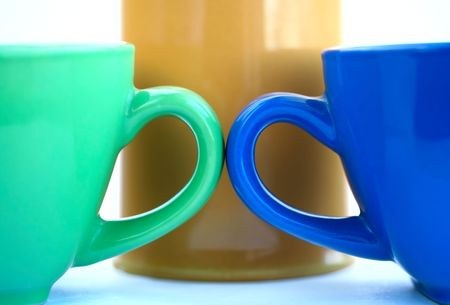 Yellow, green  and blue cups on a white background isolated