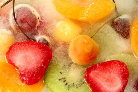Mix of berries and fruit in ice, background