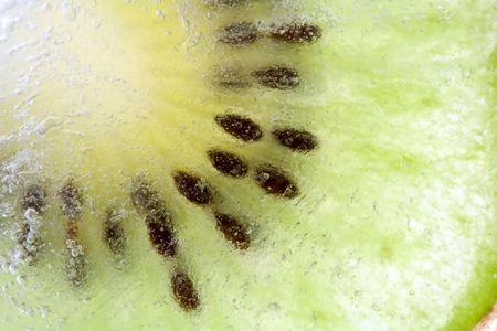 Slice kiwi inside ice, macro, background Stock Photo