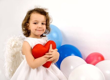 A little angel-girl embracing red heart, colour balloon around