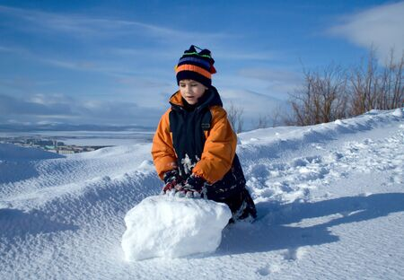 Portrait of the boy with a snowball on a background of polar mountains