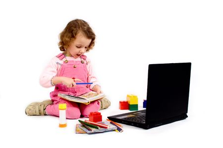 A little girl with computer, pencils, CD, school writing-materials around Stock Photo